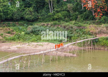 LUANG PRABANG, LAOS - MAY 16 2015: Buddhist monks cross a wooden bridge on the Nam Ou river in Luang Prabang in - Stock Photo