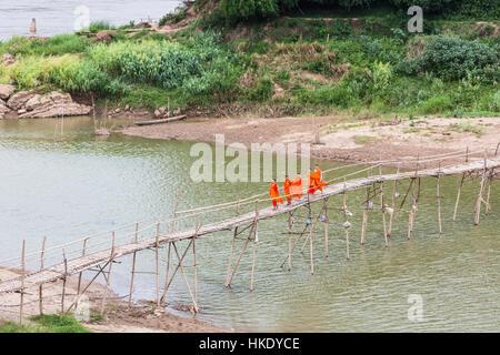 LUANG PRABANG, LAOS - MAY 16 2015: Buddhist monks cross a wooden bridge on the Nam Ou river in Luang Prabang in - Stock Photo