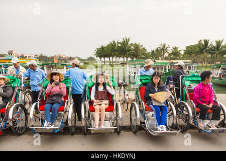 HOI AN, VIETNAM - FEBRUARY 7, 2016: Asian tourists wait for their cyclo tour of Hoi An old town to begin. The city - Stock Photo