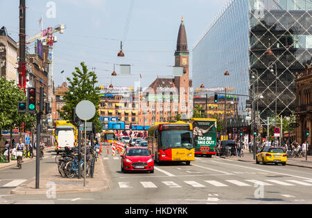 COPENHAGEN, DENMARK - MAY 24, 2016: Cars and buses wait at an intersection in front of the city hall in Denmark - Stock Photo