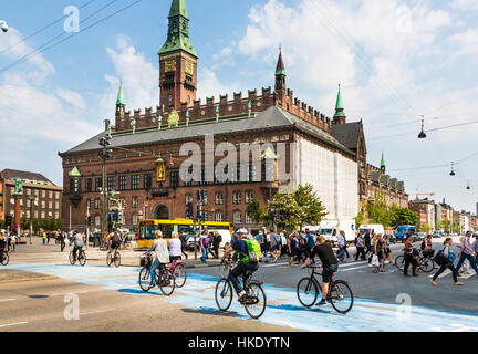 COPENHAGEN, DENMARK - MAY 24, 2016: Cyclists cross the street on a dedicated line in front of the city hall in Denmark - Stock Photo