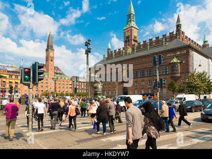 COPENHAGEN, DENMARK - MAY 24, 2016: Pedestrians cross the street in front of the city hall in Denmark capital city - Stock Photo