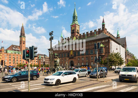 COPENHAGEN, DENMARK - MAY 24, 2016: Cars cross an intersection in front of the city hall in Denmark capital city - Stock Photo