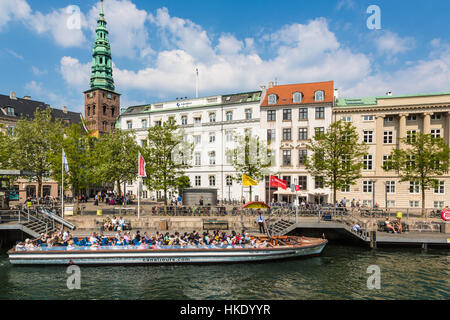 COPENHAGEN, DENMARK - MAY 24, 2016: Tourists enjoy the traditional architecture from a tourist boat along the canals - Stock Photo