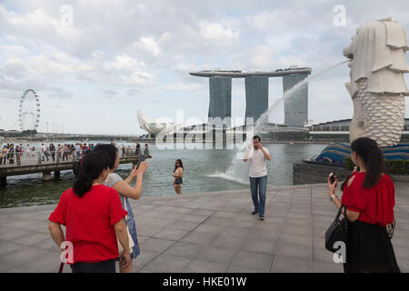 SINGAPORE, SINGAPORE - FEBRUARY 22 2016: Tourists take photo in front of the Marina Sands building and the Merlion - Stock Photo