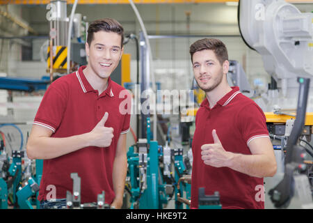 technicians stand in industry environment with robots while holding their thumbs up - Stock Photo