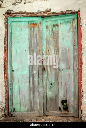 Old green damaged wooden doors in one of the colonial buildings in La Gomera island, Spain - Stock Photo