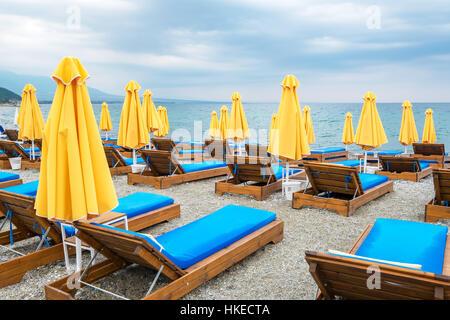 Beach umbrellas and empty lounge chairs on a cloudy day. Platamonas, Pieria, Macedonia, Greece, Europe - Stock Photo
