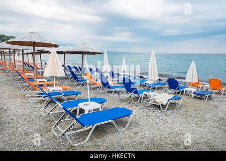 Empty beach chairs and umbrellas. Greece - Stock Photo