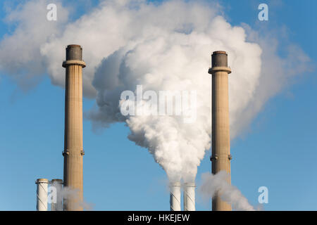 The pipes of a factory with white smoke as a global warming concept. - Stock Photo