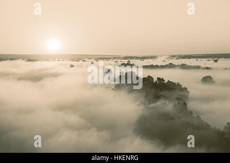 Sunrise over hills and trees covered by fog. Sepia toned image. - Stock Photo
