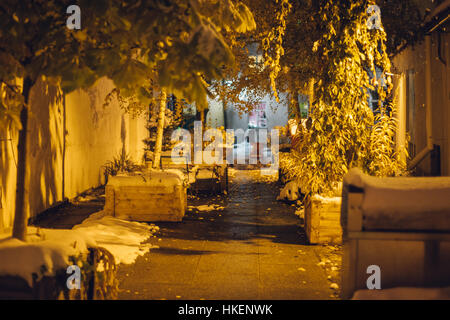 Cosy courtyard covered by first snow. Night scene, selective focus - Stock Photo