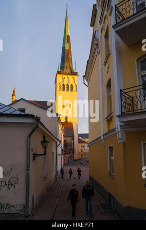 TALLINN, ESTONIA - 01 MAY 2016: Sunset in old town. People are walking along narrow streets. St. Olaf (Oleviste) - Stock Photo