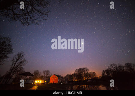 Night shot of wooden cottages and starry sky. - Stock Photo