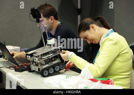 Sofia, Bulgaria - December 17, 2016: A student prepares her race robot during an open competition of self-made robots - Stock Photo