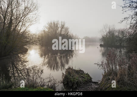 Weak winter sun rises across a lake on a  cold, foggy morning - Stock Photo