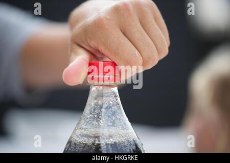 hand unscrewing bottle cap. cold drink, beverage, plastic bottle, coke. - Stock Photo