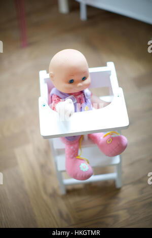 doll in baby chair. toy, children's room, wooden floor, childhood. - Stock Photo