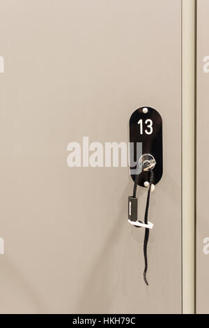 Grey Cabinets with Numbered Locks and Keys in School, Gym or Locker Room - Stock Photo