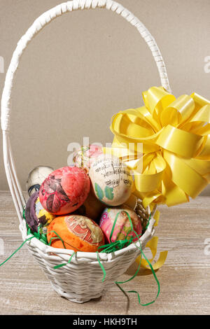 Decoupage decorated colorful Easter eggs in wicker basket - Stock Photo