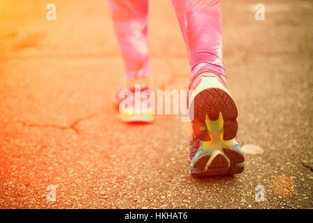 Runner feet running on road closeup on shoes. Woman fitness sunrise jog workout wellness concept. - Stock Photo