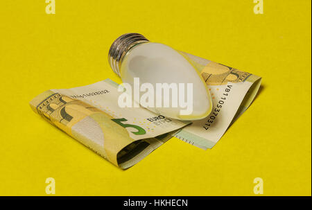 On a yellow background are five euro banknotes and electric incandescent lamp - Stock Photo