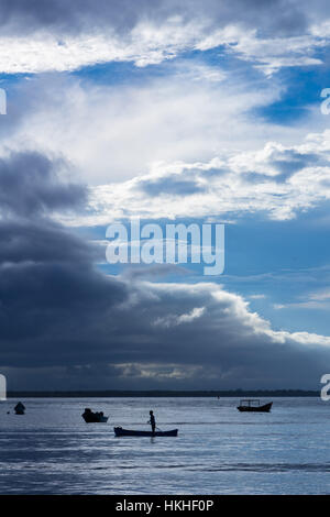 Fisherman going out to sea in his small boat, Ilha do Mel, Paraná, Brazil, South America - Stock Photo