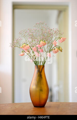 Amber glass fluted vase with flowers in a room - Stock Photo