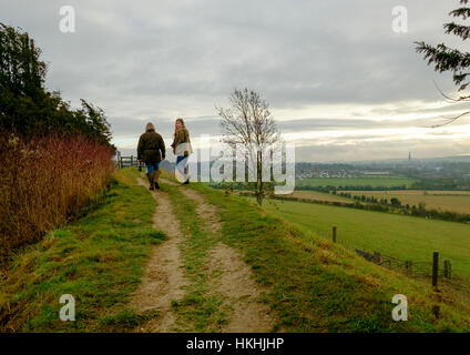 Walkers on the earthworks at Old Sarum, the city of Salisbury in the background - Stock Photo
