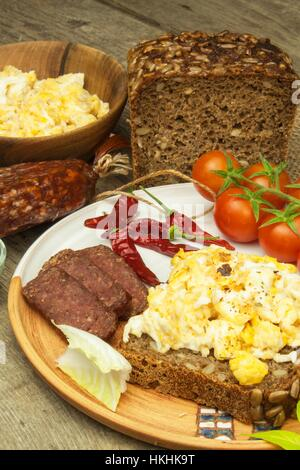 Scrambled eggs with bread and salami. Egg breakfast on a wooden table. Healthy food. - Stock Photo