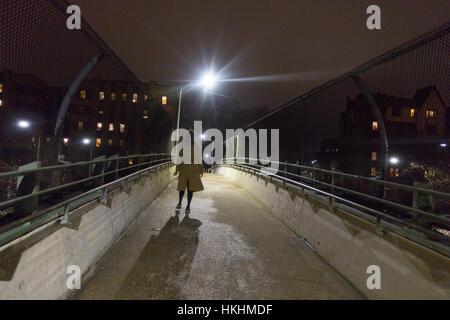 Woman walks over a pedestrian bridge at night in the Windsor Terrace neighborhood of Brooklyn, NY. - Stock Photo