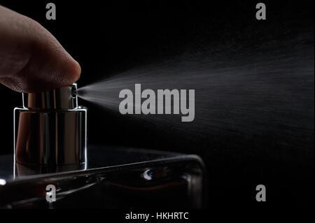 nozzle spray perfume on black close up - Stock Photo