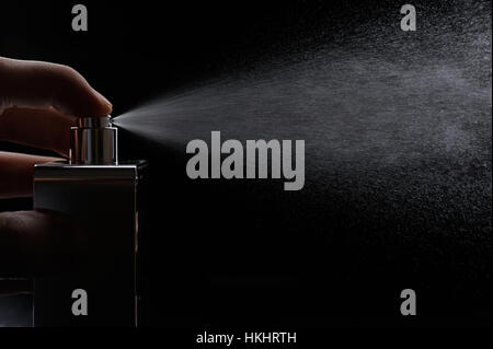 spray perfume on black background close up - Stock Photo