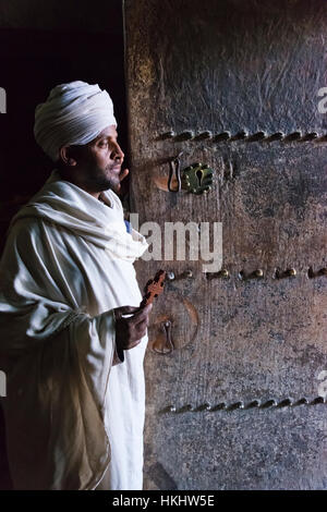 Priest in Yemrehanna Kristos Church, built inside a natural cavern, Lalibela, Ethiopia - Stock Photo