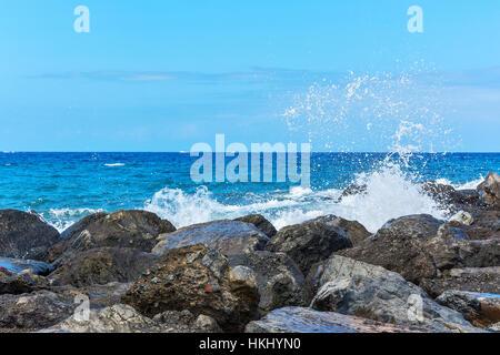 Splashes of water breaking on coastal rocks - Stock Photo