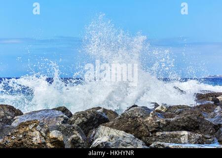 Waves breaking in splashes on the coastal rocks - Stock Photo