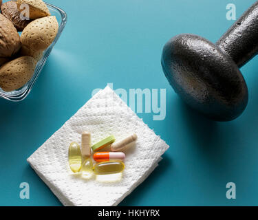 Closeup on dumbbell, nuts and dietary supplements on blue background: fitness and weight loss concept. - Stock Photo