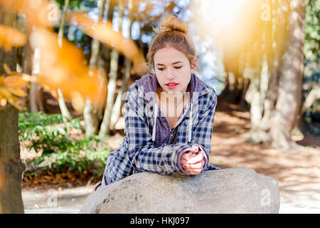 This young teenage girl hangs out alone in a park, sitting on a rock in a thoughtful disengaged position thinking - Stock Photo