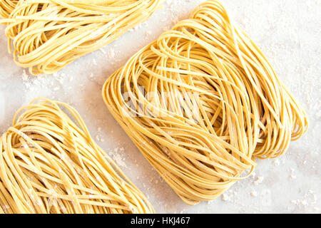 Homemade Raw Egg Noodles on a white background close up - Stock Photo