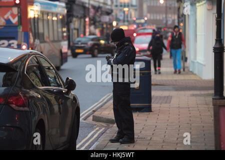 Traffic warden issues ticket - Stock Photo