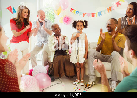 Multi-ethnic family clapping for girl singing karaoke with microphone at birthday party - Stock Photo