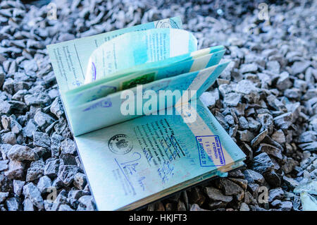 Lost passport on a stoney path open at a page with a Canadian Visa - Stock Photo