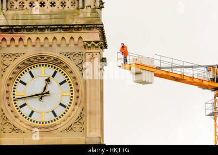 A man watches an event from the top of a tower crane behind a clock tower. - Stock Photo