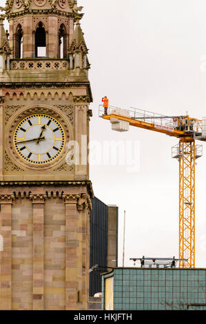 A man uses binoculars to watch an event below him from the top of a tower crane behind a clock tower. - Stock Photo