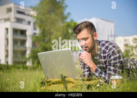 Young man working on laptop and lying in park, Munich, Bavaria, Germany - Stock Photo