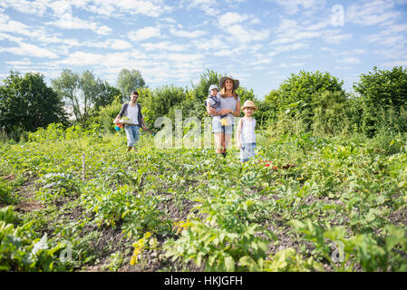 Family walking in community garden, Bavaria, Germany - Stock Photo
