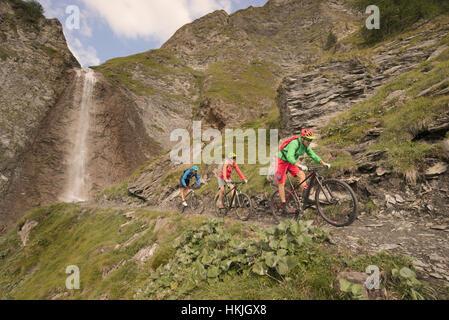 Three mountain bikers riding on hill at waterfall, Zillertal, Tyrol, Austria - Stock Photo