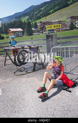 Mountain bikers relaxing after biketour and her friend cleaning bicycles, Zillertal, Tyrol, Austria - Stock Photo