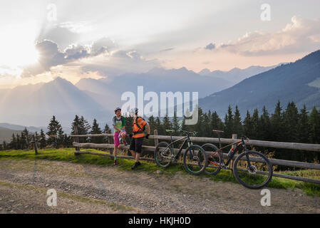 Young couple of mountain bikers standing by wooden fence during sunset, Zillertal, Tyrol, Austria - Stock Photo