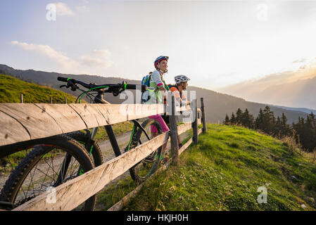 Young couple of mountain bikers standing by wooden fence looking at view during sunset, Zillertal, Tyrol, Austria - Stock Photo